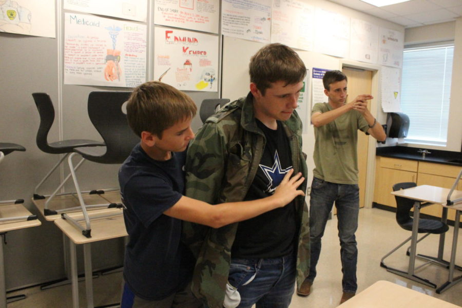 Connor Benningfield (10) searches Tanner Wollard (11) for illegal items, while  Matthew Pilcher (10)  watches the vehicle.